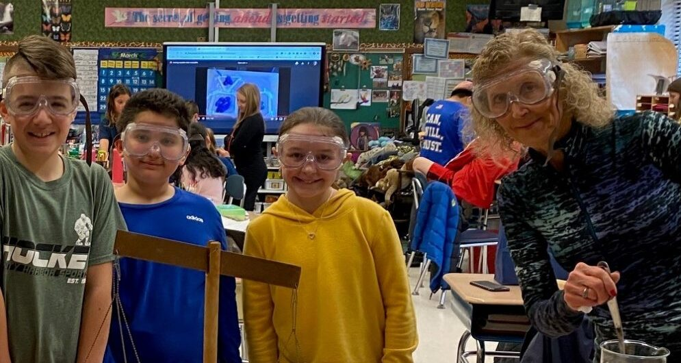 A teacher and students with googles